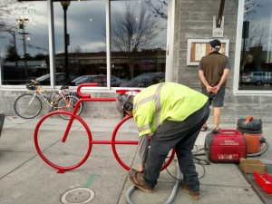 Public Works' Mark Matherly installs the Dero Bike Bike Rack at Little Star Solano while Francesco Papalia checks out the menu!