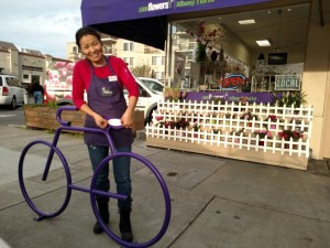 Albany Florist and Gifts' owner, Zagdaa Baatar, puts the decal on her brand new Bike Bike Rack!!